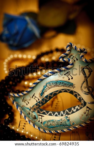 Ornate carnival mask on a music paper with rose and pearls - stock photo