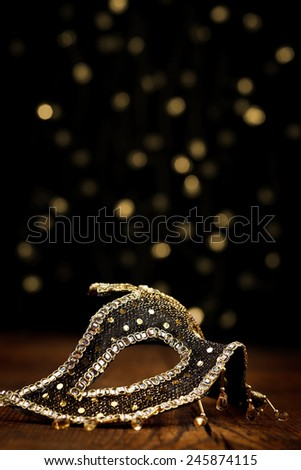 Ornate carnival mask with festive lights on black background - stock photo