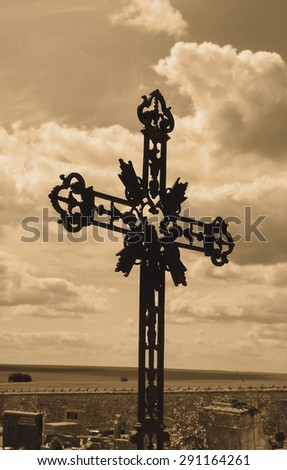 Ornate cast iron cross at French cemetery and sun glow through the clouds. Aged photo. Sepia. - stock photo