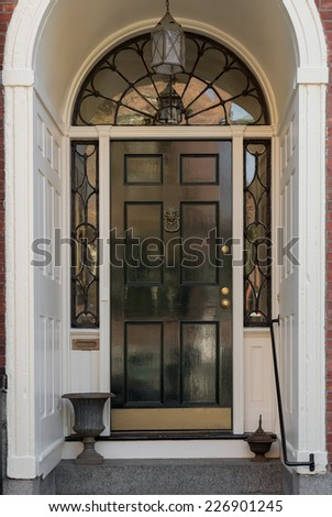 Ornate Entryway with Shiny Black Front Door, Overhead Lunette, and Hanging Lamp in White Archway - stock photo