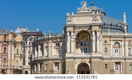 Ornate facade of historical curved building with sculptures, domed roof and pillared balcony