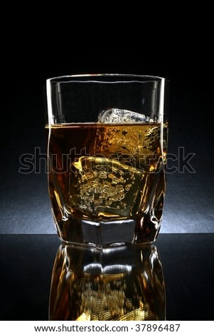 Ornate glass of whiskey and ice against black background. - stock photo