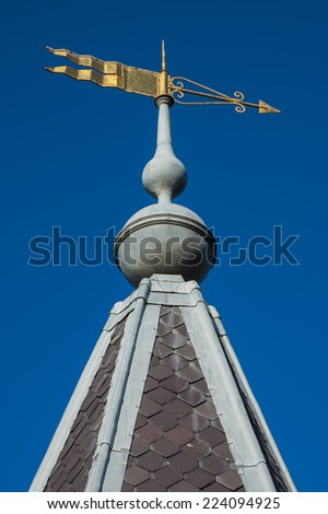 Ornate gold weather vane pointing to the right and attached to the apex of a traditional tile and lead roof set against a clear blue sky - stock photo