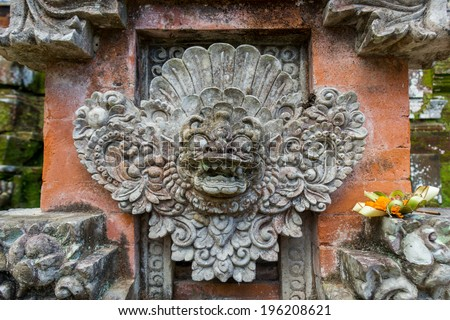 Ornate intricately carved and decorated stone column in formal Balinese garden or park with lush green tropical vegetation - stock photo