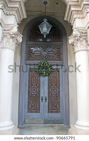 Ornate Iron work covering double door entrance with Christmas wreath and gothic columns - stock photo