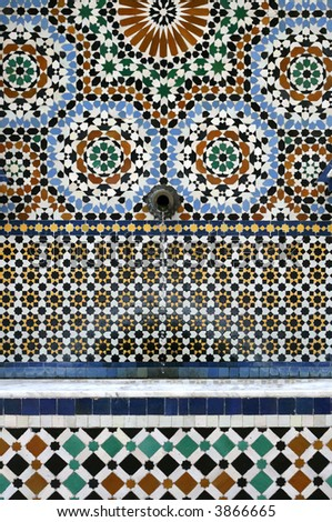 ornate Moroccan-styled mosaic tiled fountain - some water mineral white staining at splash arc - stock photo