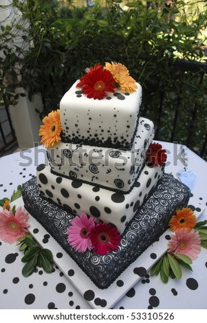 Ornate multi-tiered wedding cake with black polka-dots - stock photo