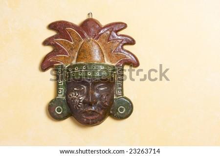 Ornate Myan Mask Hanging on a Light Yellow Wall - stock photo