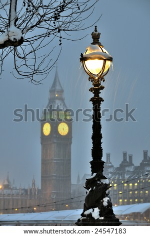 Ornate pedestal of a dolphin lamp standard on the South Bank of the River Thames, London, England, in the snow.  The sculpture around the base of the standard is actually the model of a sturgeon. - stock photo