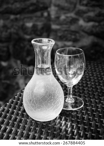 Ornate pitcher with wine and one empty glass on wicker table in front of rough stone wall in rustic restaurant. A game of light and shadow. Selective focus on the pitcher. Aged photo. Black and white. - stock photo