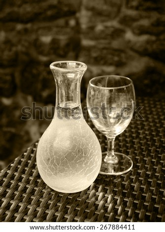 Ornate pitcher with wine and one empty glass on wicker table in front of rough stone wall in rustic restaurant. A game of light and shadow. Selective focus on the pitcher. Aged photo. Sepia. - stock photo