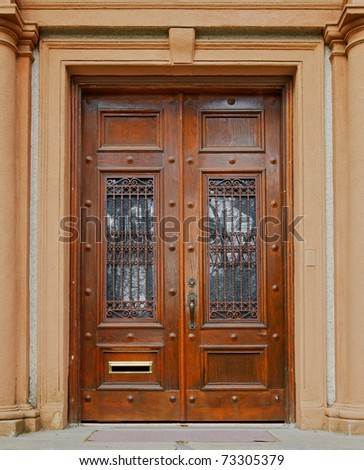 Ornate stained wood doors with wrought iron grating over glass windows - stock photo