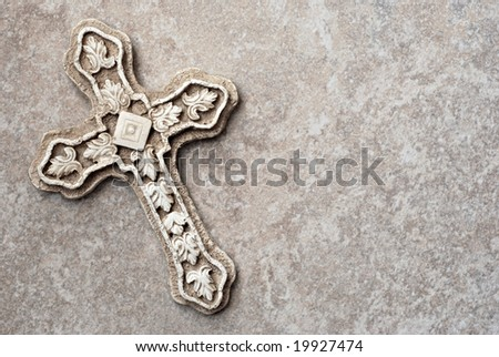Ornate stone cross on marble background with copy space. - stock photo