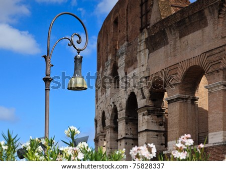 Ornate street lamp with Colosseum in background - stock photo