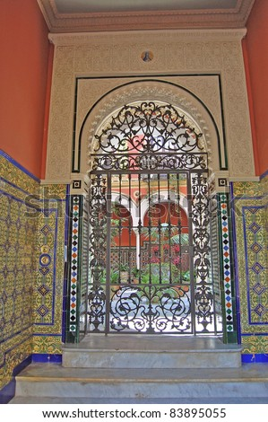 Ornate tile work in the gated entrance to a private Spanish courtyard garden in Seville. - stock photo