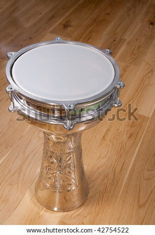 Ornate turkish silver drum on a wooden floor - stock photo
