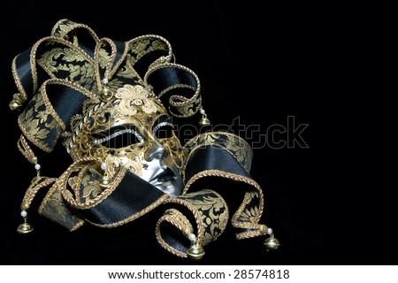 Ornate venetian mask lying on black background - stock photo