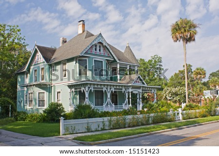 ornately detailed Victorian style home with lush landscape - stock photo