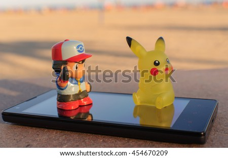 OROPESA DEL MAR - JULY 2016: pokemon go pikachu and Ash Ketchum real with a smartphone - stock photo