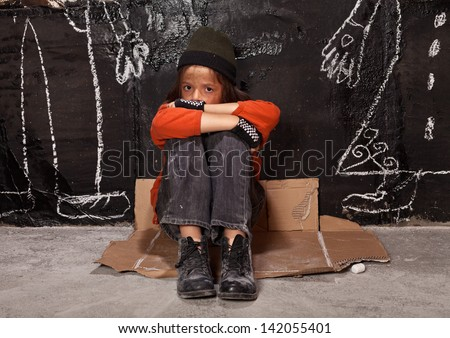 Orphan child on the street concept - boy sitting by the wall with drawn parent figures - stock photo