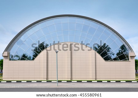 Orsha, Belarus - July 16, 2016: Sport Complex. Facade of circular shape of modern building. The design of arched roof and wall with glass and sandwich panels. - stock photo
