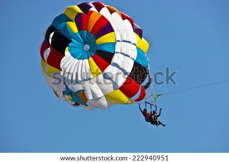 ORTACA, TURKEY - OCTOBER 2, 2014: Two young unidentified women parasailing with multicoloured parachute over water. - stock photo