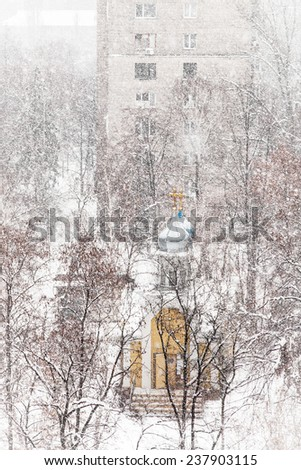 Orthodox chapel in the city park during a snowfall - stock photo