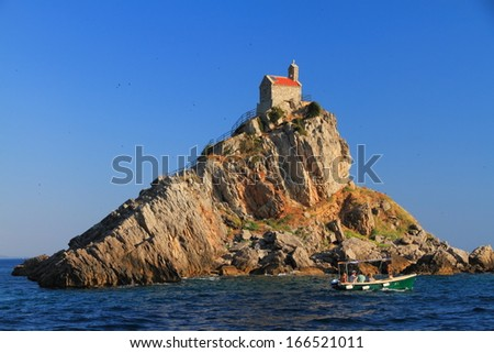 Orthodox church built on top of isolated island on Mediterranean sea - stock photo