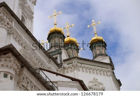 Orthodox church tower's cupola and gold crosses on a grey clouds with a blue gleam behind them - stock photo