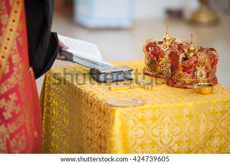 Orthodox Church wedding paraphernalia - cross, bible and crowns - stock photo