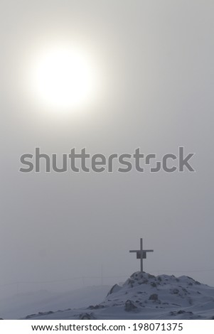 Orthodox cross on the rocks in the Antarctic sunny foggy day - stock photo