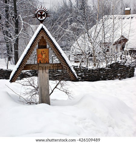 Orthodox Icon of the Mother of God with Child on a carved wooden cross on the outskirts of the village under the snow - stock photo