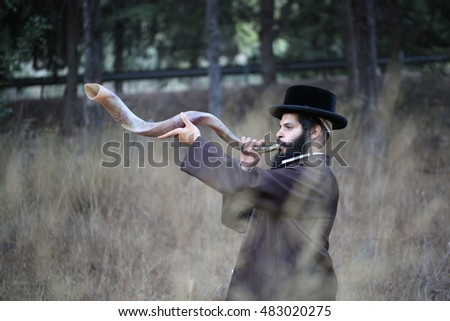 orthodox Jew blowing the shofar of Rosh Hashanah. indistinct man in background blur blows a long yemenite shofar horn with focus on the open end of the horn; isolation on forest.