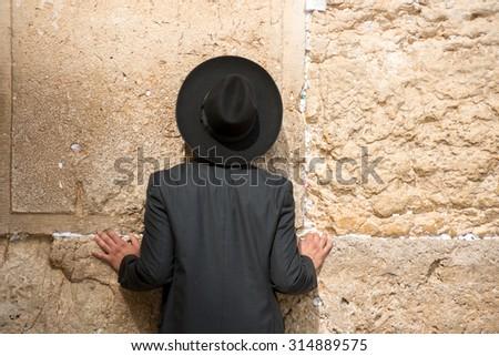 Orthodox Jew praying and reading Torah at the Wailing Wall, Jerusalem, Israel - stock photo