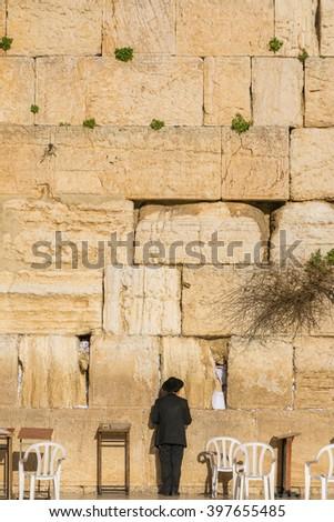 Orthodox Jewish man prays in the wailing wall of Jerusalem, Israel - stock photo
