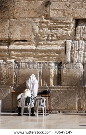 Orthodox Jewish worshipers pray at the Wailing Wall in Jerusalem - stock photo