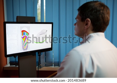 Orthopaedist at work with computer. He modeling orthopedic shoe using foot scan - stock photo
