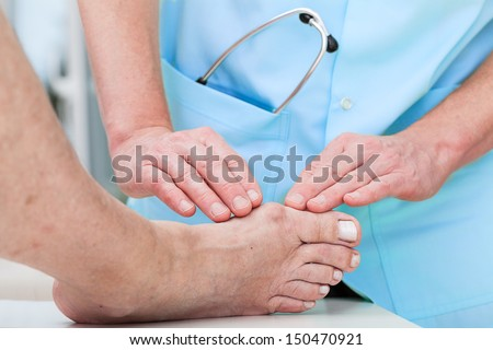 Orthopedist at work checking patient's foot - stock photo