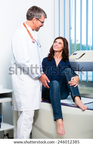 Orthopedist doctor making ultrasonic image on patient in surgery - stock photo