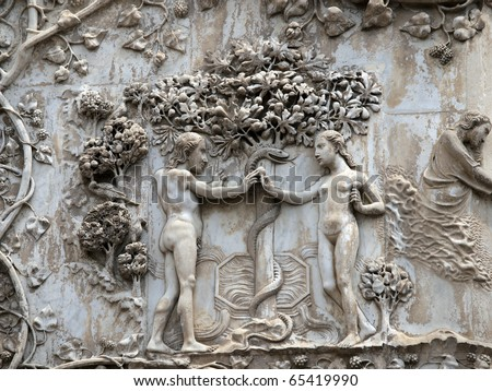 orvieto - Duomo facade. The first pillar: scenes from Genesis.Eve offers the forbidden fruit to Adam. - stock photo