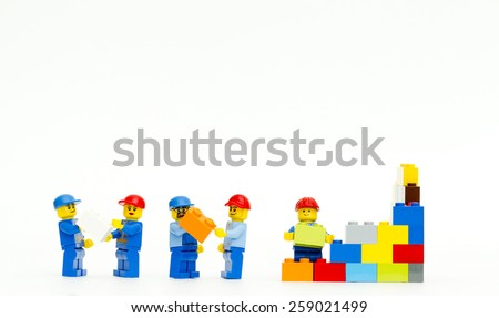 Orvieto, Italy - March 8th 2015: group of workman Lego mini figure build a wall. Lego is a popular line of construction toys manufactured by the Lego Group - stock photo