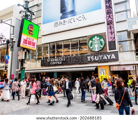 OSAKA - APRIL 12: Starbucks coffee shop in Dotonbori shopping street on April 12, 2014 in Osaka, Japan.  The first store of Starbucks outside the USA or Canada opened in Tokyo, Japan  in 1996 - stock photo
