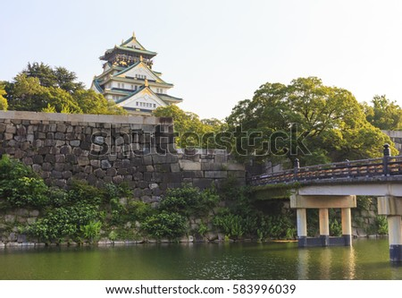 Osaka Castle with wooden Gokurakubashi Bridge in front of the castle during summer season, this castle is very famous tourist attraction of Osaka, Japan.