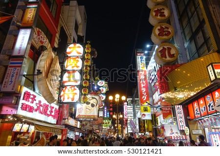 OSAKA, JAPAN - APRIL 13, 2016: Crowds walk below the signs of Dotonbori. With a history reaching back to 1612, the district is now one of Osaka's primary tourist destinations.