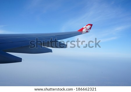 OSAKA JAPAN MARCH 11 2014:AirAsia plane flying in sky over Kansai Airport, Osaka on 11 Mar 2014.AirAsia is one of the company that ready for the open of AEC by flying to most of the country in Asia - stock photo