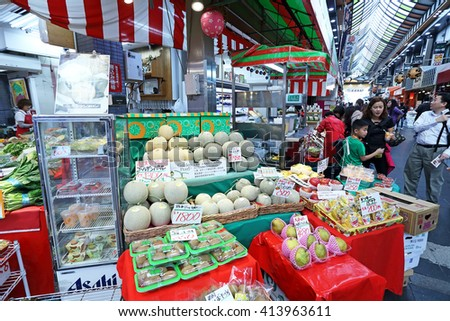 OSAKA, JAPAN - NOV 6: Tourists shopping and visit vegetables and fruits prices in shop  in Kuromon Ichiba market on November 6, 2015 in Osaka, Japan. it is market places popular in Osaka - stock photo