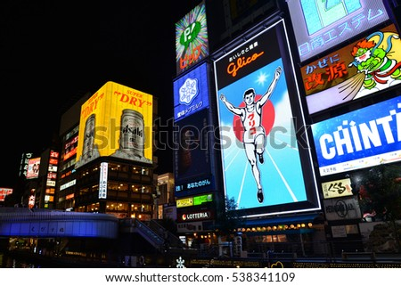 Osaka, Japan - November 16, 2016: Glico Man sign is seen along the river with many billboards, in Dotombori area, famous shopping and restaurant area, in Osaka, Japan