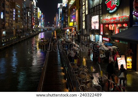 OSAKA, JAPAN - 30 NOVEMBER 2014: People line up outside a restaurant besides a river in Osaka. The vibrant nightlife is a tourist attraction in this second largest city in Japan. - stock photo
