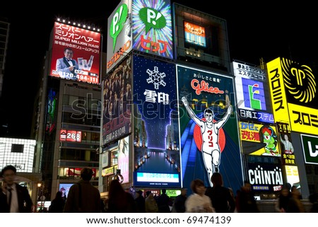 OSAKA, JAPAN - OCTOBER 28: The famous Glico Man billboard and other neon displays in Dotonbori on October 28, 2010 in Osaka, Japan. Dotonbori is a popular entertainment district for tourists. - stock photo