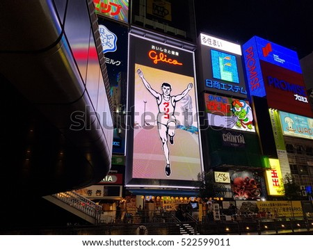 OSAKA, JAPAN-September 12th,2016 : People wander in Dotonbori area during raining with famous Glico billboard in the visibility. Dotonbori is now Osaka's primary tourist destination.
